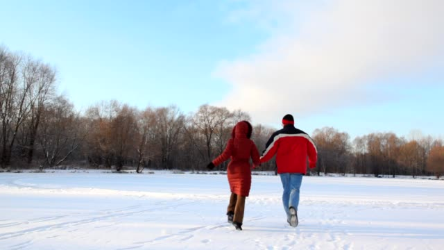 Couple having joined hands runs on snowfield video