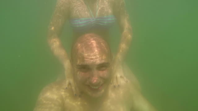 couple havng fun in water on vacation video