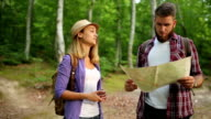 Couple Hikers making a plan with a hiking map in forest video