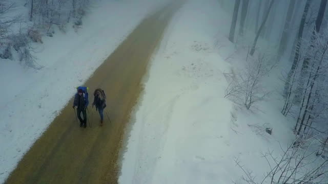 Couple hiking outside in winter nature, aerial view video