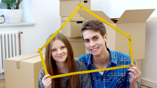 Couple holding folding ruler shaped like house video