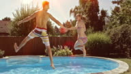 SLO MO DS Couple holding hand and jumping into pool video