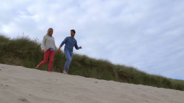 Couple holding hands and running down sand dunes towards sea in slow motion video