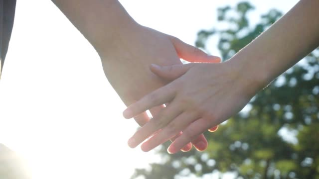 Couple holding hands at sunny day in slow motion video