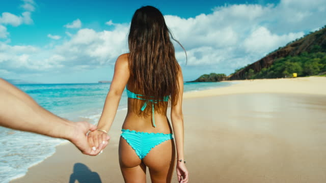 Couple holding hands at the beach, slow motion POV video