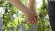 Couple holding hands in park video