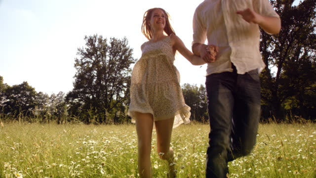 SLO MO DS Couple holding hands running across high grass video