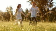 SLO MO TS Couple holding hands running across summer meadow video