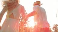 SLO MO Couple holding hands running towards sun video