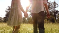 SLO MO Couple holding hands walking across summer meadow video