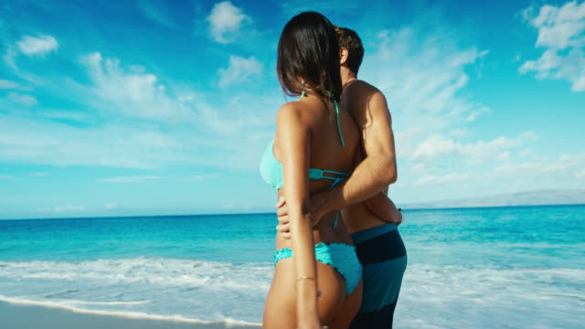 Couple holding hands walking down tropical beach in slow motion video