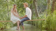SLO MO DS Couple holding hands while sitting on footbridge video