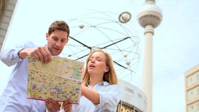 Couple holding map and discussing video
