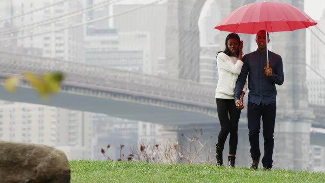 A couple holds hands and an umbrella as they walk through the park towards the camera with the Brooklyn Bridge behind them, in slow motion video