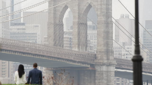 A couple holds hands and walks through the park with the Brooklyn Bridge in front of them video