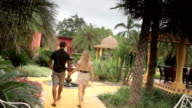 Couple holiday walking through Morrocan style hotel grounds video