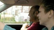 Couple in car talk smile and laugh and man leaves video