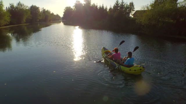 AERIAL: Couple in kayak rowing along calm river towards the beautiful summer sunset video