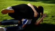 Couple in love makng summersault, tumble and handsprings on grass in slow motion video
