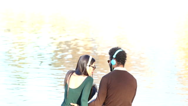 Couple in love sitting by lake and listening to music with headphones video