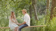 SLO MO TD Couple in love sitting on a footbridge video