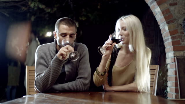Couple in love smiles, makes toast with wine and kisses in rural farm-house, tuscany, italy, at night - slow-motion HD video footage video