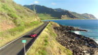 AERIAL: Couple in red convertible car driving along the beautiful coastal road video