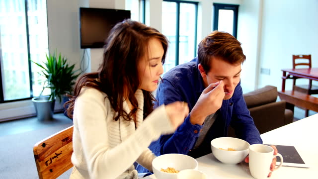 Couple interacting while having breakfast in living room video
