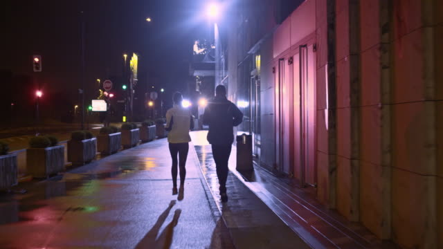 TS Couple jogging in city streets on a rainy night video
