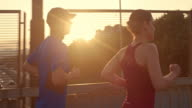SLO MO TS Couple jogging in the city at sunset video