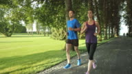 SLO MO TS Couple jogging in park on sunny day video