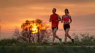 SLO MO TS Couple jogging in countryside at sunset video