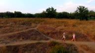 Couple jogging through grassland on a footpath video