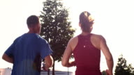 SLO MO TS Couple jogging through city on sunny day video