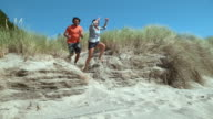 Couple jumping off sand dune in super slo mo video