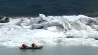 Couple kayaking by icebergs and glacier, Alaska video