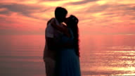 Couple kissing at sunset. Couple beach sunset. Kissing silhouette. Love couple video