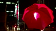 Couple kissing behind a red umbrella in town video