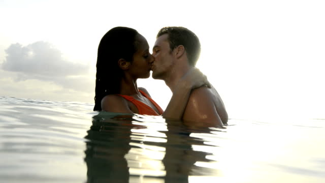 Couple kissing in the sea at sunset video