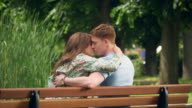 Couple kissing on bench video
