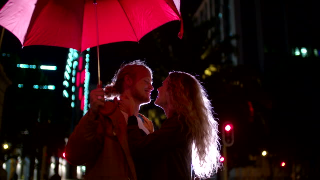 Couple kissing under a red umbrella in town video