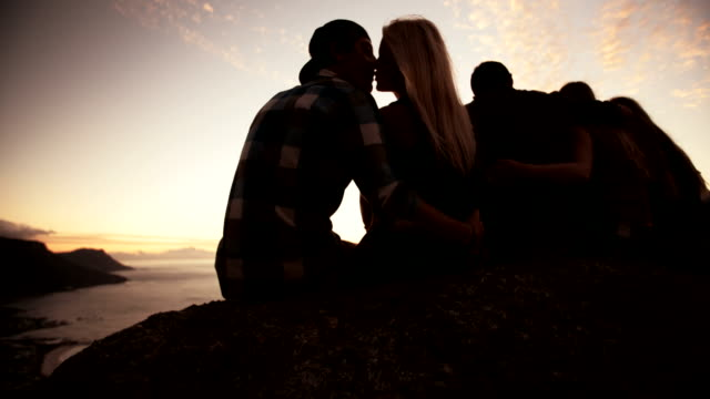 Couple kissing with group of friends sunset video