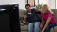 Couple laughing at TV video