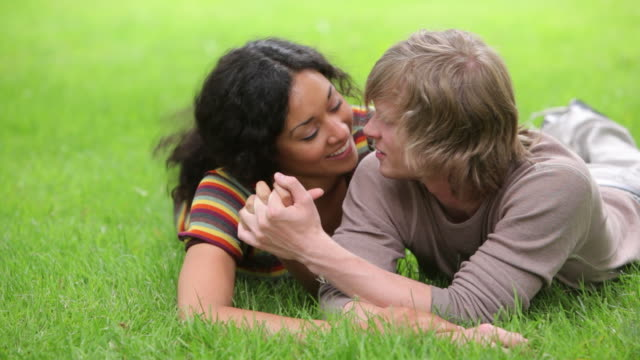Couple laying in grass together video