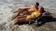Couple laying near ocean startled by waves video