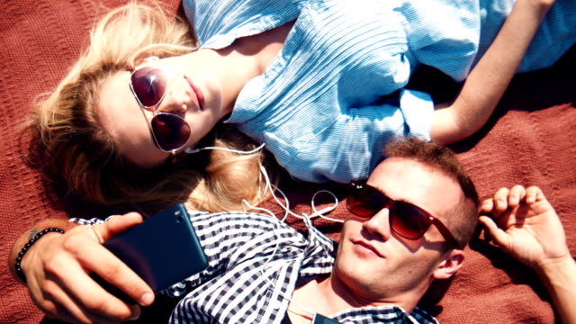 Couple listening to music and taking selfie on blanket in sunlight video