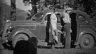1935: Couple loading black dog into car in mountainous forest. video