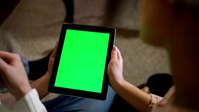 Couple look at green screen ipad on christmas eve video