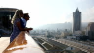 Couple look off ship railing to city below, Haifa, Israel video