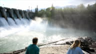 Couple look out towards hydroelectric facility at sunrise video